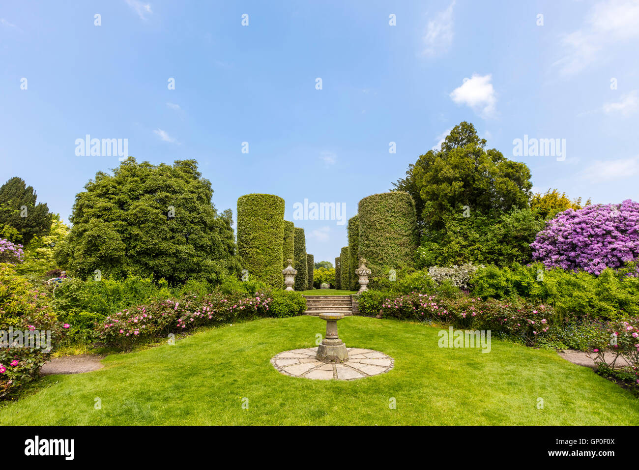 English country garden with sundial and topiary shrubs. - Stock Image