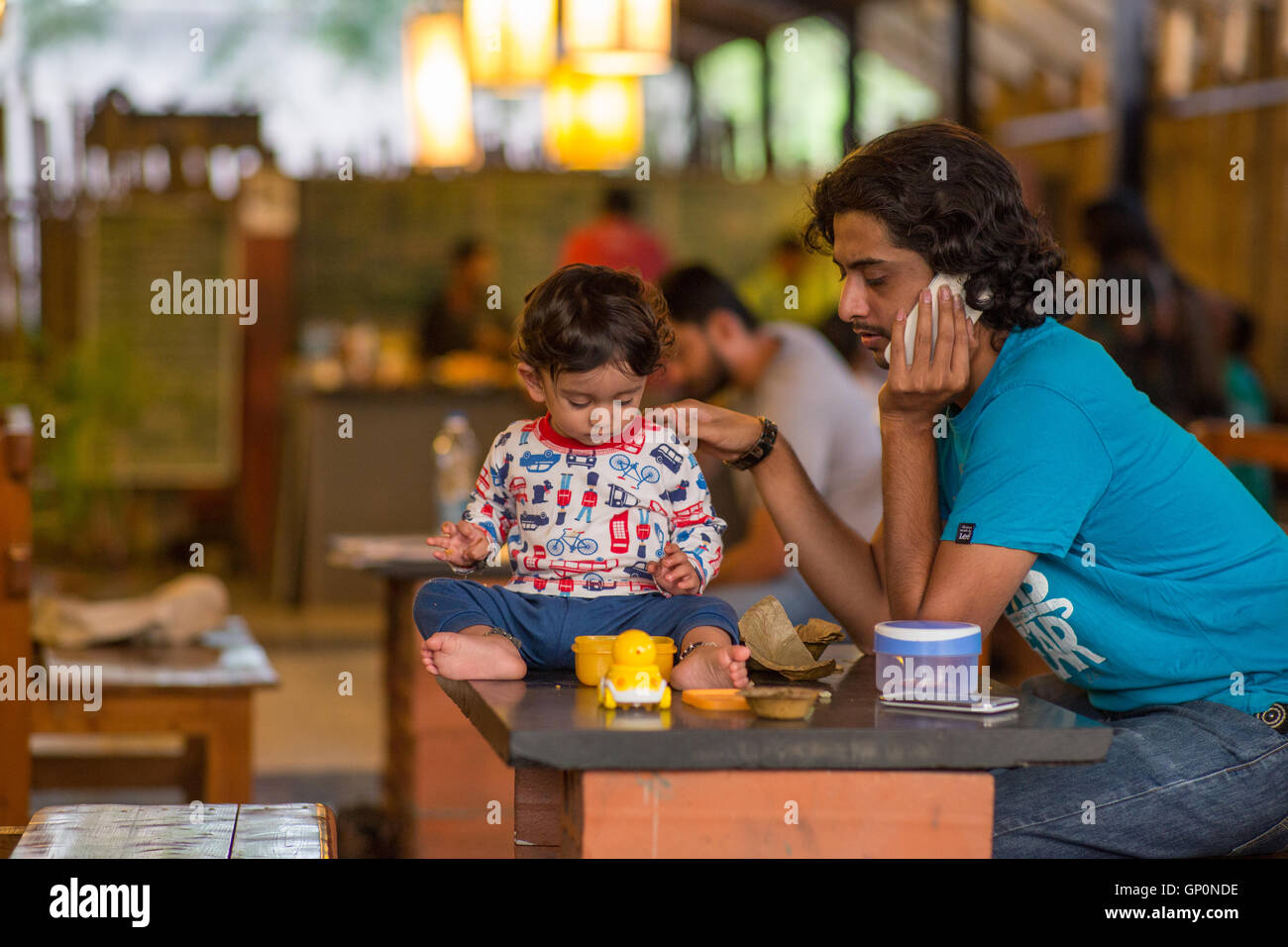 Dad talking on the phone while his baby is playing on the table at a café in Bangalore, India. - Stock Image