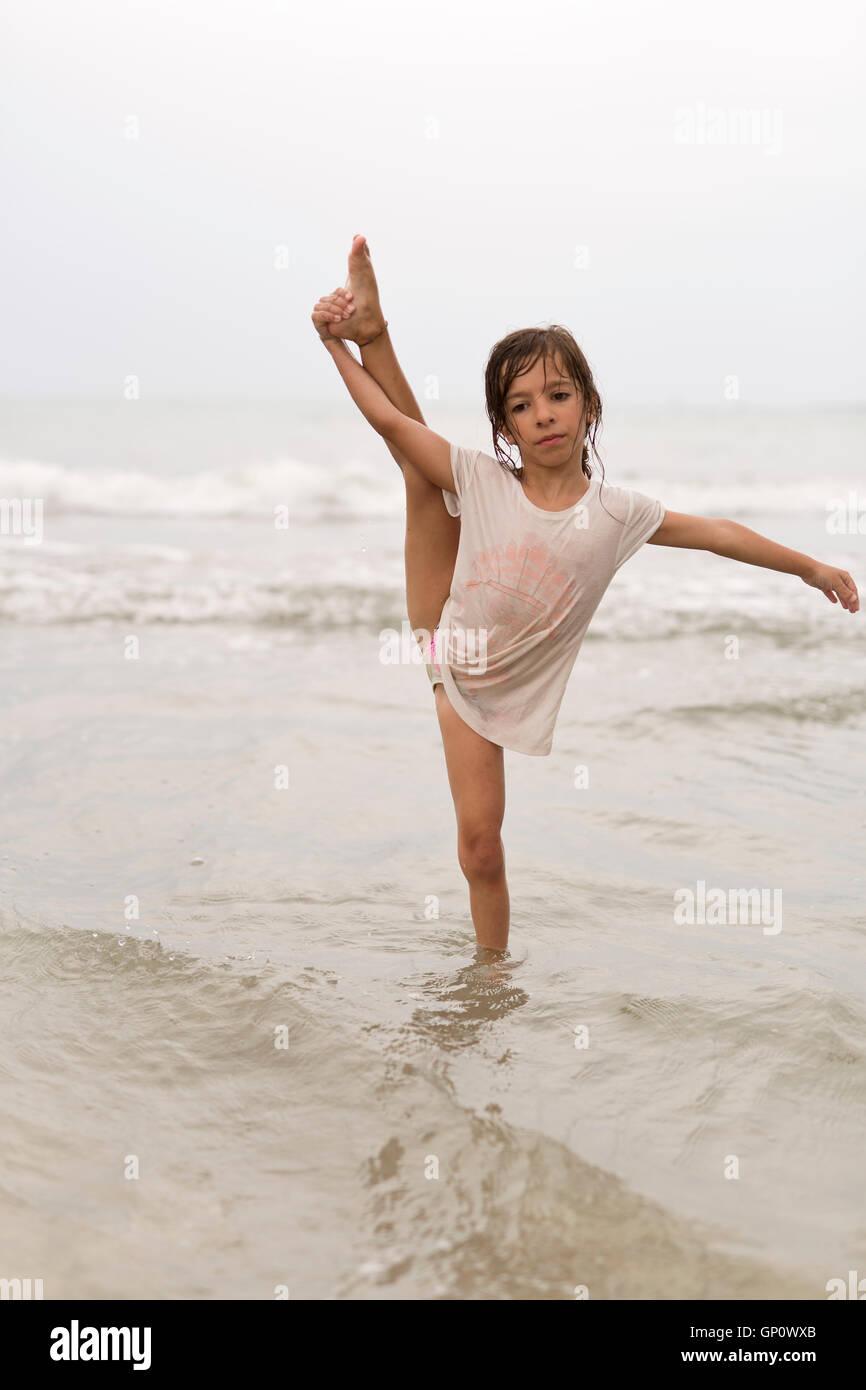 Little Girl On A Beach Doing Water Gymnastics Stock Photo