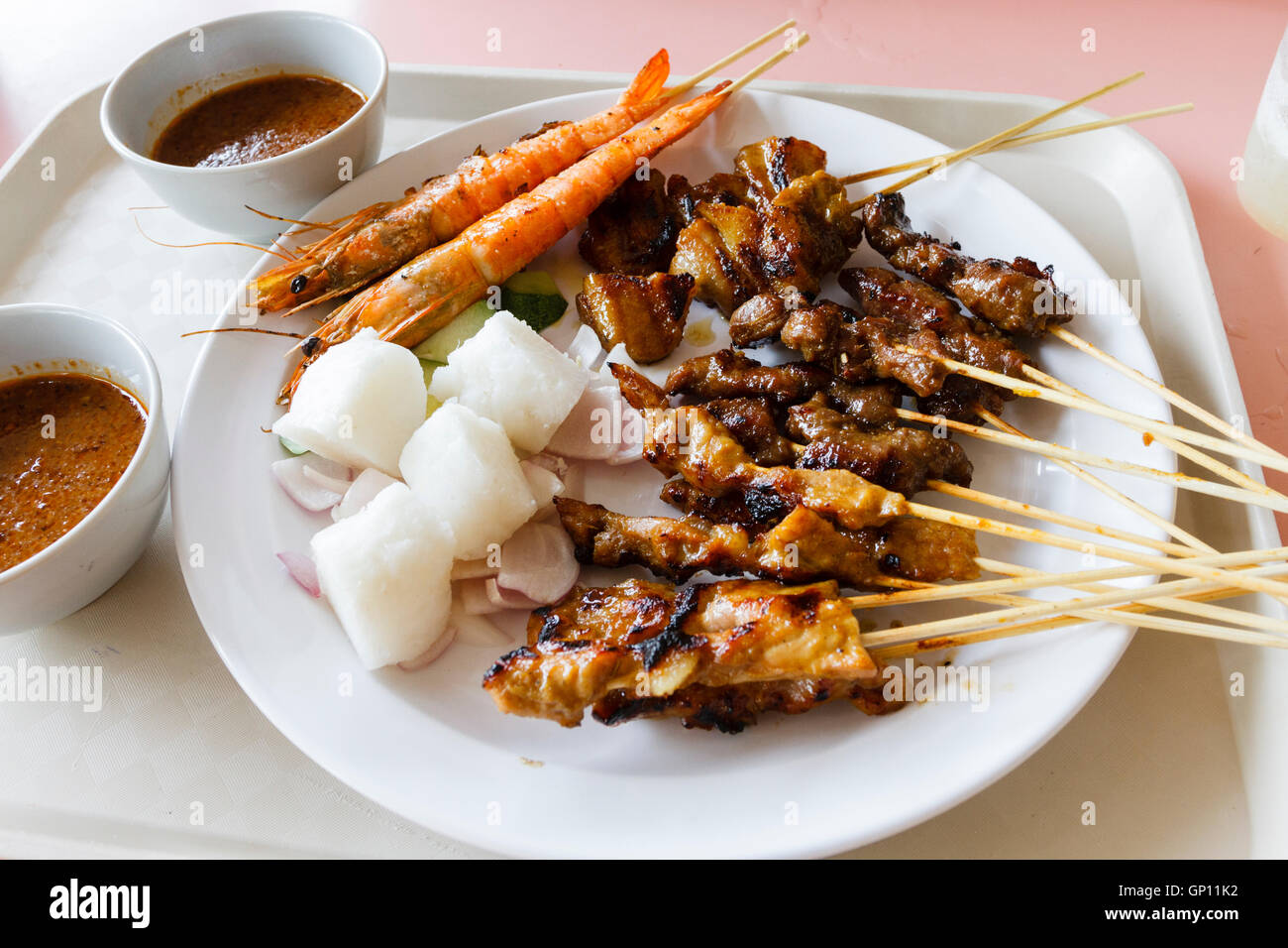 Plate of mixed satay food on a plate with bowls of satay sauce, Singapore. - Stock Image