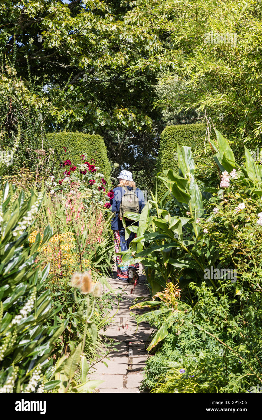 Visitors to Great Dixter garden navigate the enchanting narrow paths, plants and hedging, Northiam, East Sussex, - Stock Image