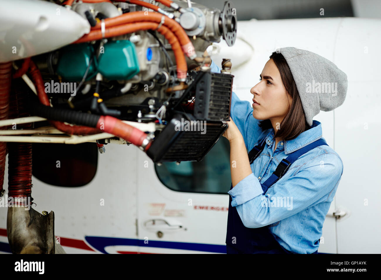 Young woman in uniform fixing something in air jet motor - Stock Image