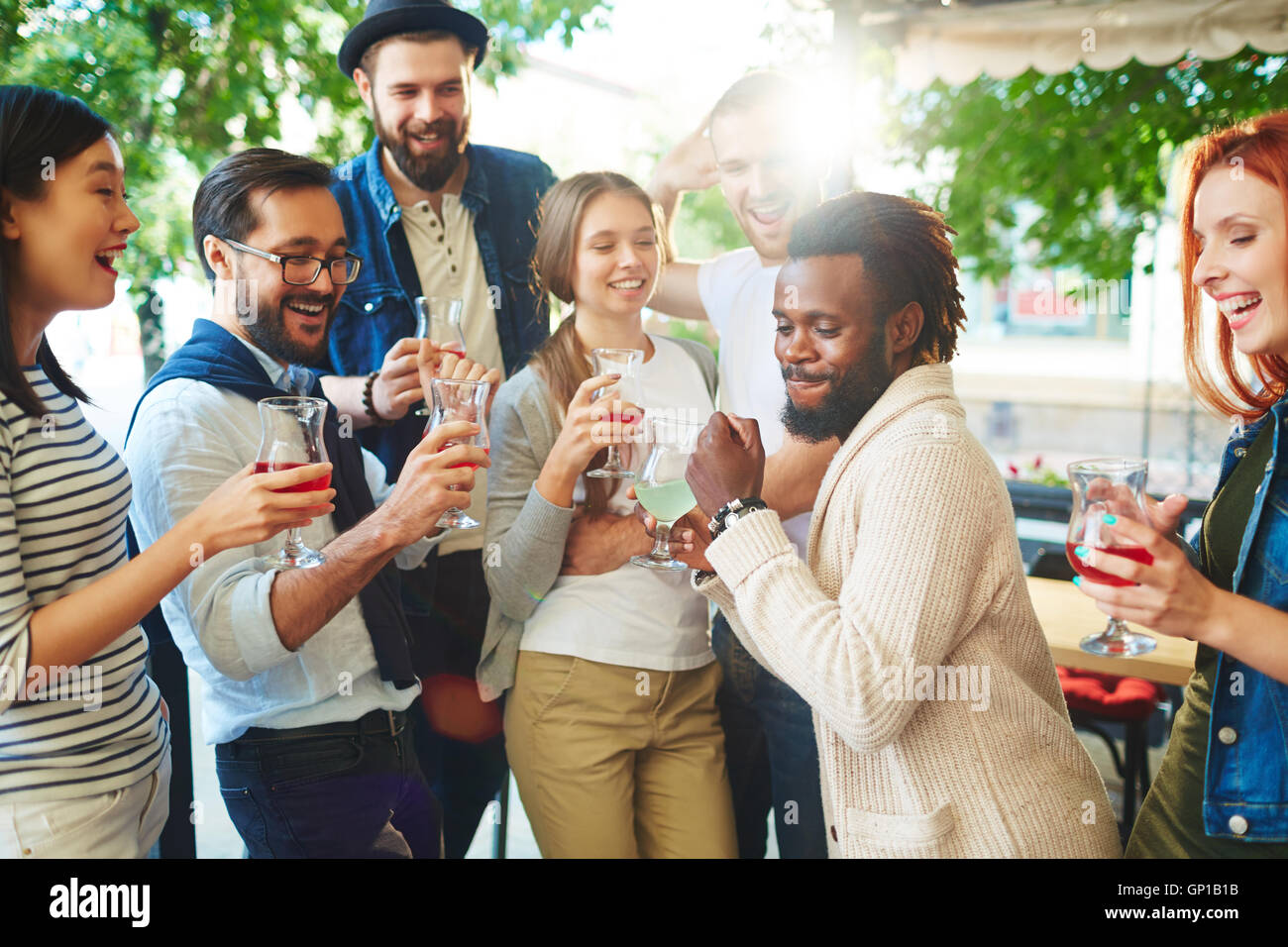 Intercultural friends having nice time in outdoor cafe - Stock Image