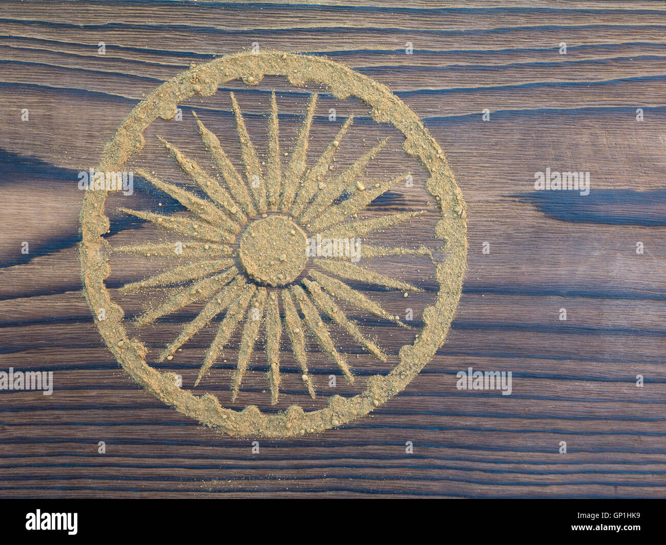Indian henna powder in the form of Ashoka Chakra on the textured wooden board - Stock Image