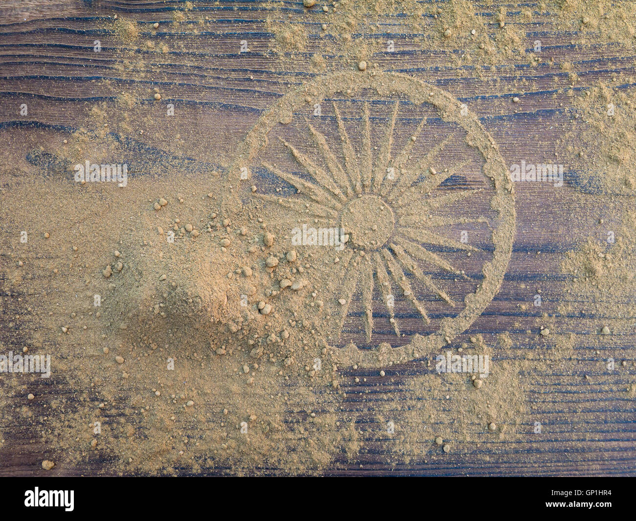Indian henna powder forms Ashoka Chakra wheel on the textured wooden board - Stock Image
