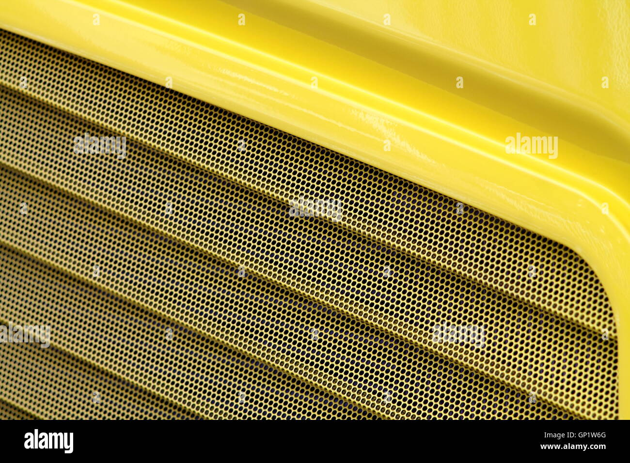 Macro of yellow lack surface of a bus with ventilation. - Stock Image