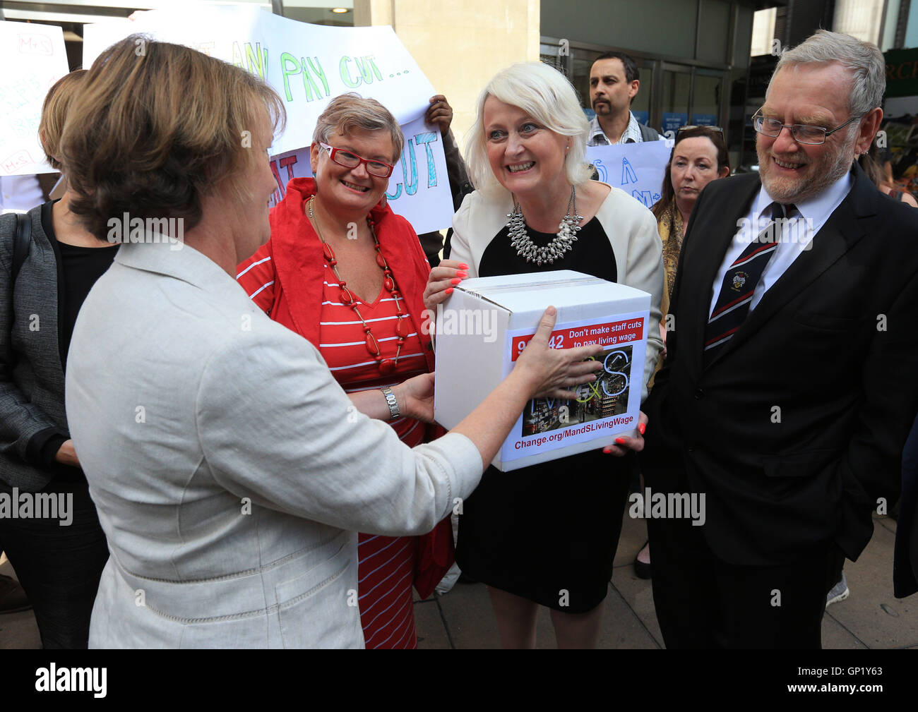 A group including MP Siobhain McDonagh (centre right) hands in a petition to Deborah Warman, Head of Reward outside - Stock Image