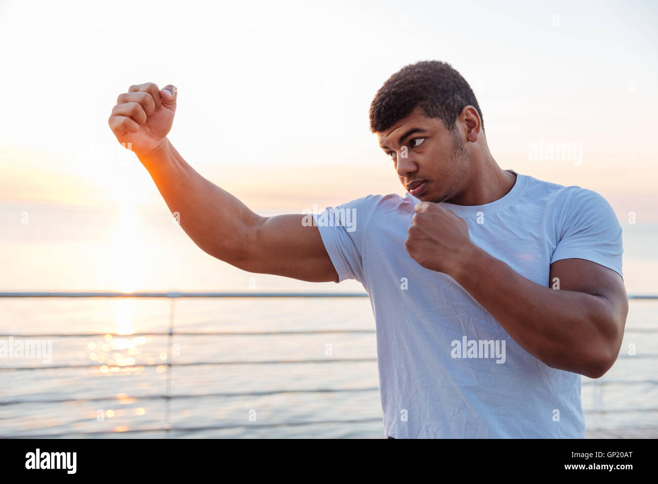 Concentrated african american young man boxer working out outdoors on sunrise - Stock Image