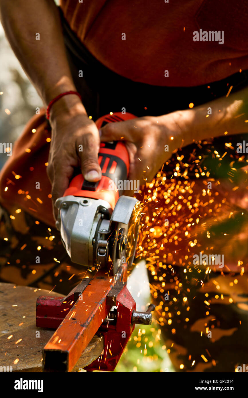 A latin american  man grinding a peace of metal with his tools - Stock Image