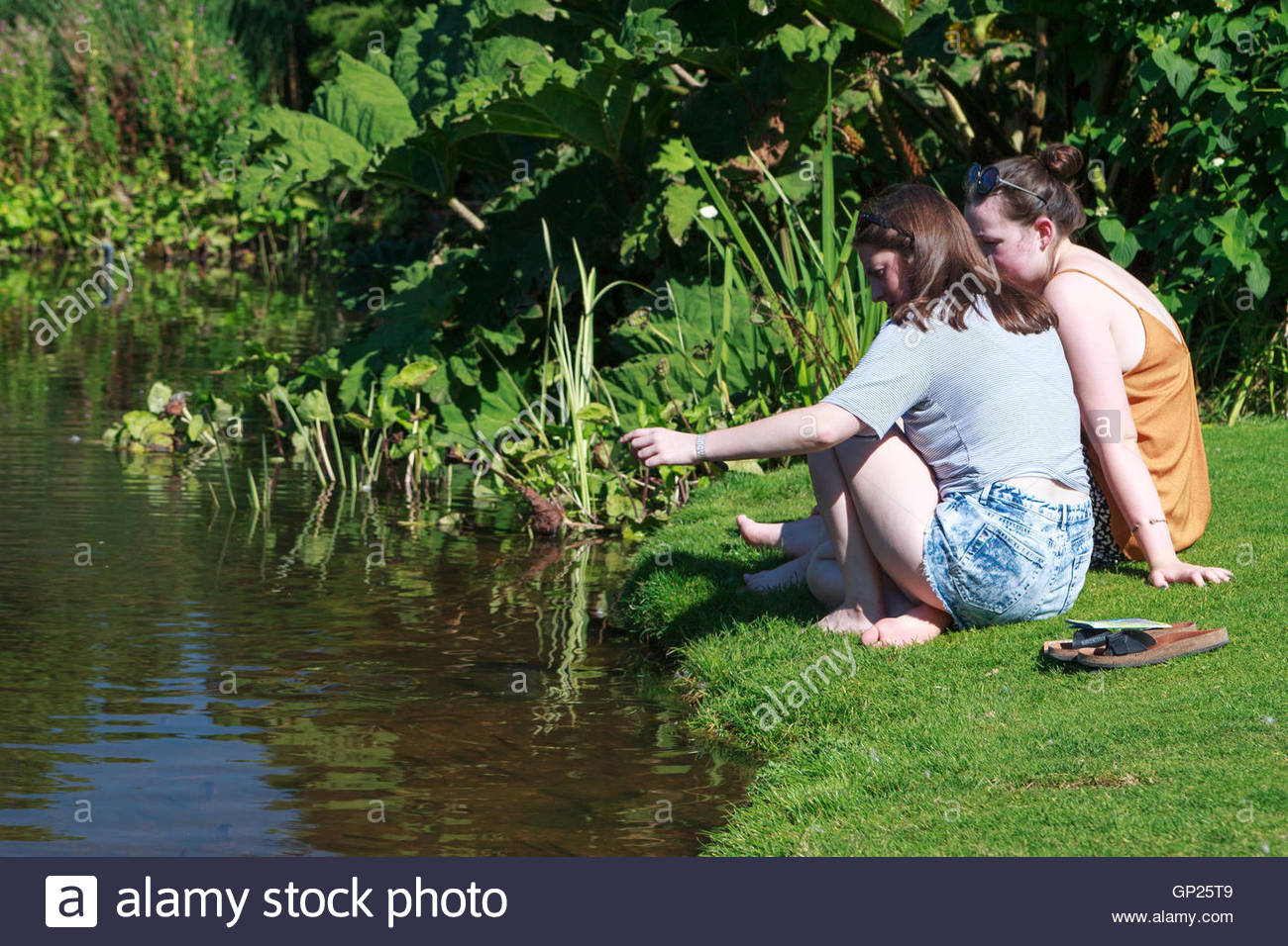 On a hot summer day in an English garden two young women are sat at the edge of a pond deep in conversation. - Stock Image