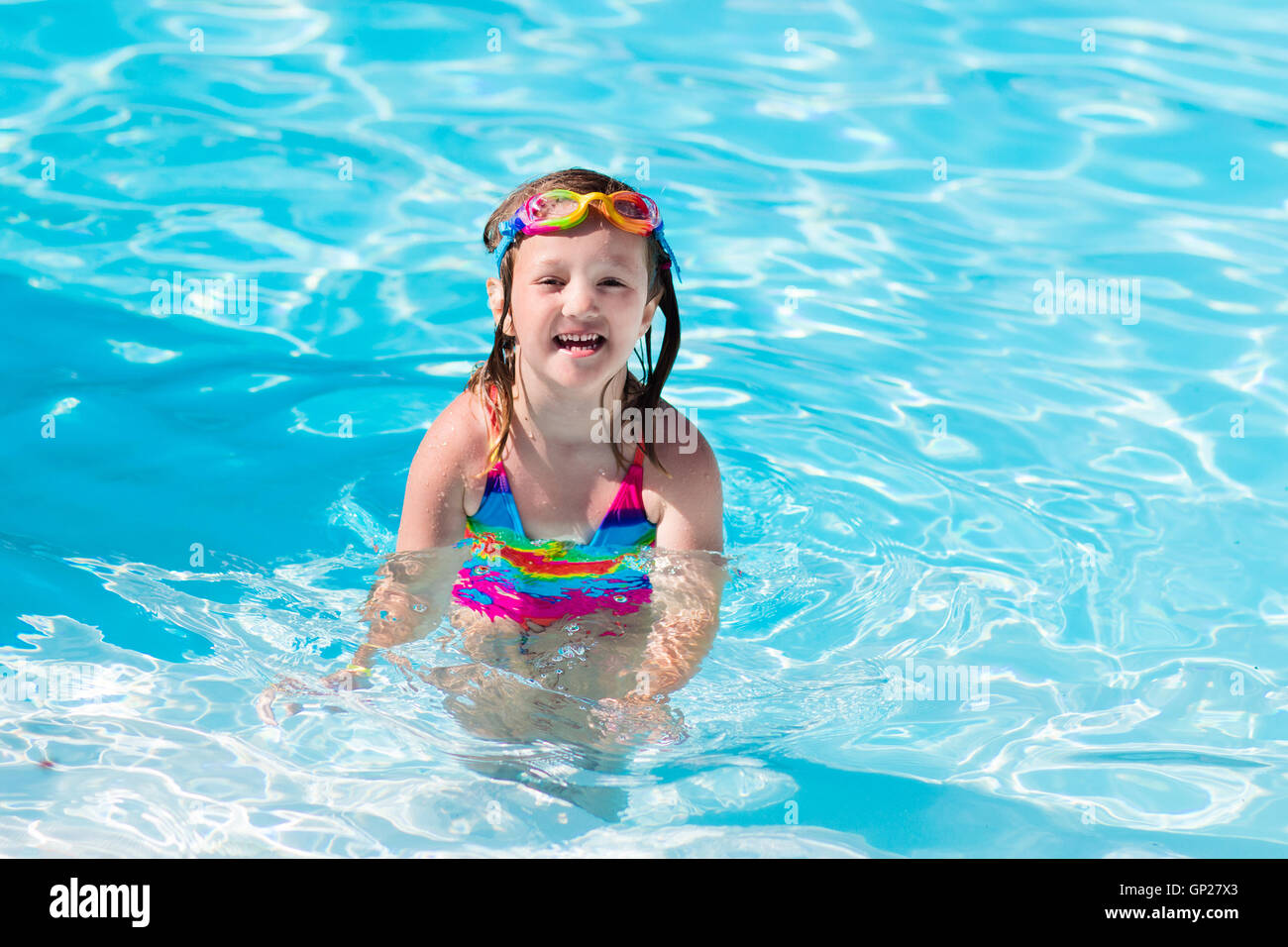 aae5959ae7 Happy little girl learning to swim and dive in outdoor swimming pool on hot  summer day in tropical resort. Child wearing goggles