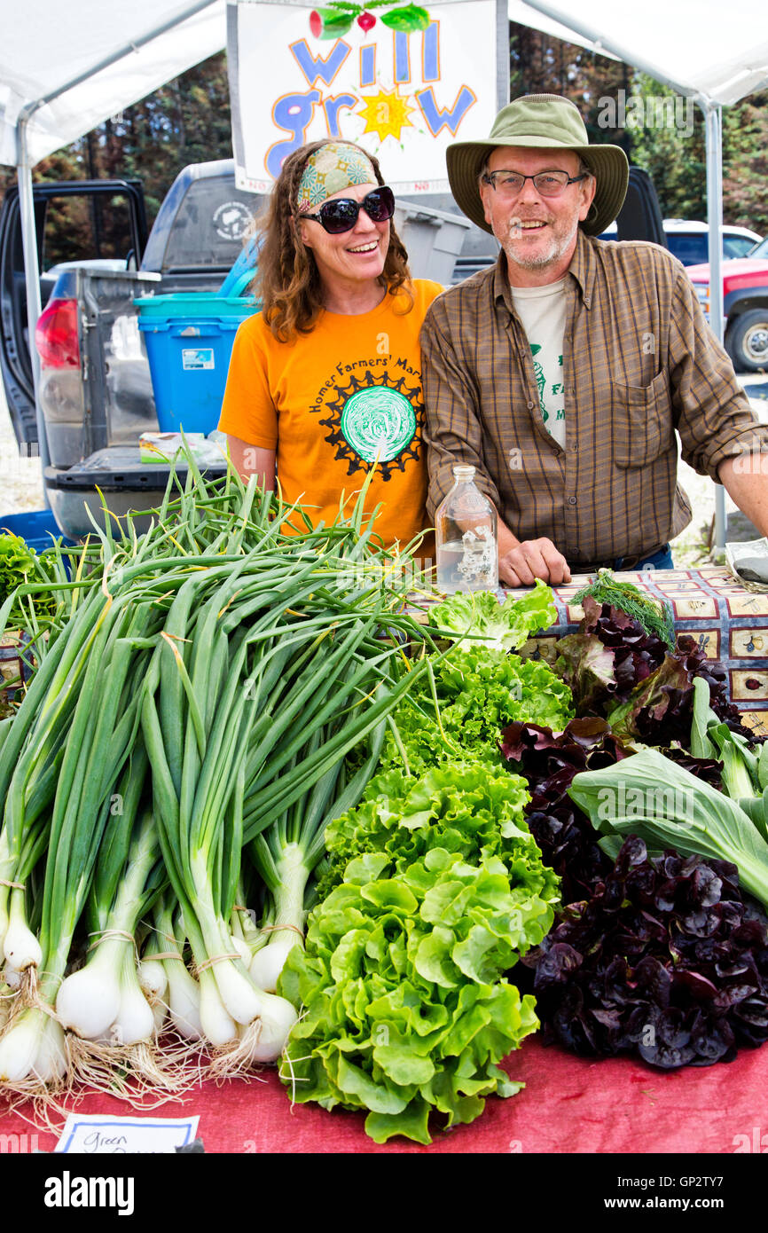 selling Farming couple selling their vegetables, farmer's market. - Stock Image