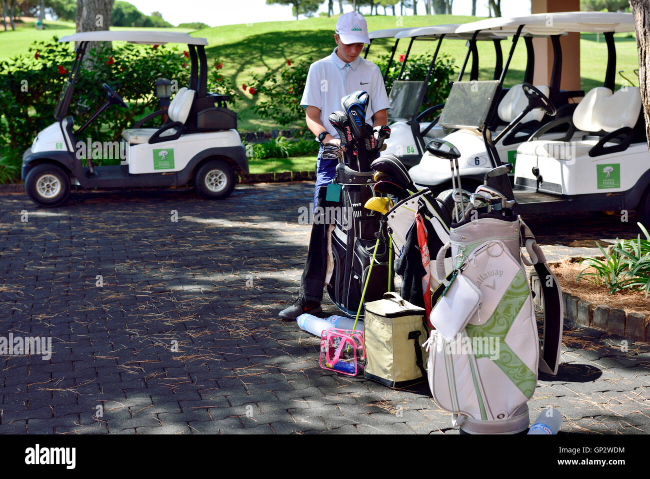 Young man with golf bags and cart at Cascatas Golf Resort & Spa, Vilamoura, Algarve, south Portugal - Stock Image