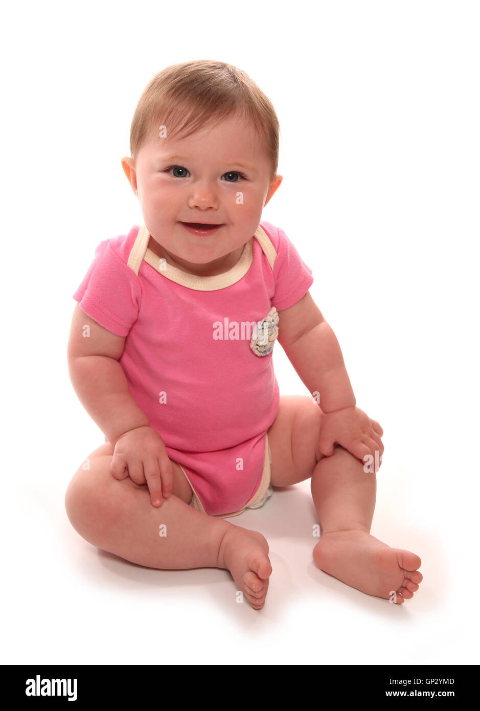 Baby girl in pink vest sitting cutout - Stock Image