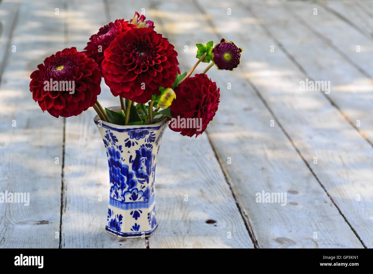 Home garden burgundy dahlias in a delft pottery vase under dappled shade. - Stock Image