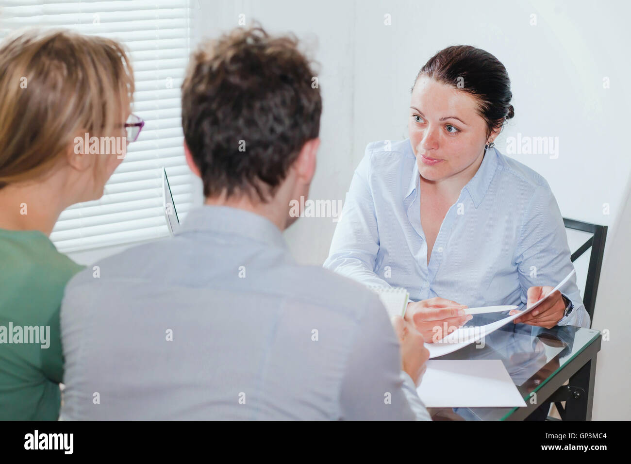 consultant or real estate agent working with couple of customers in the office - Stock Image