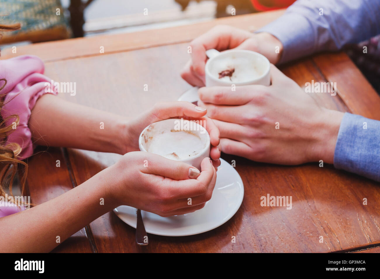 people drinking coffee in cafe, closeup of couple hands with cups - Stock Image