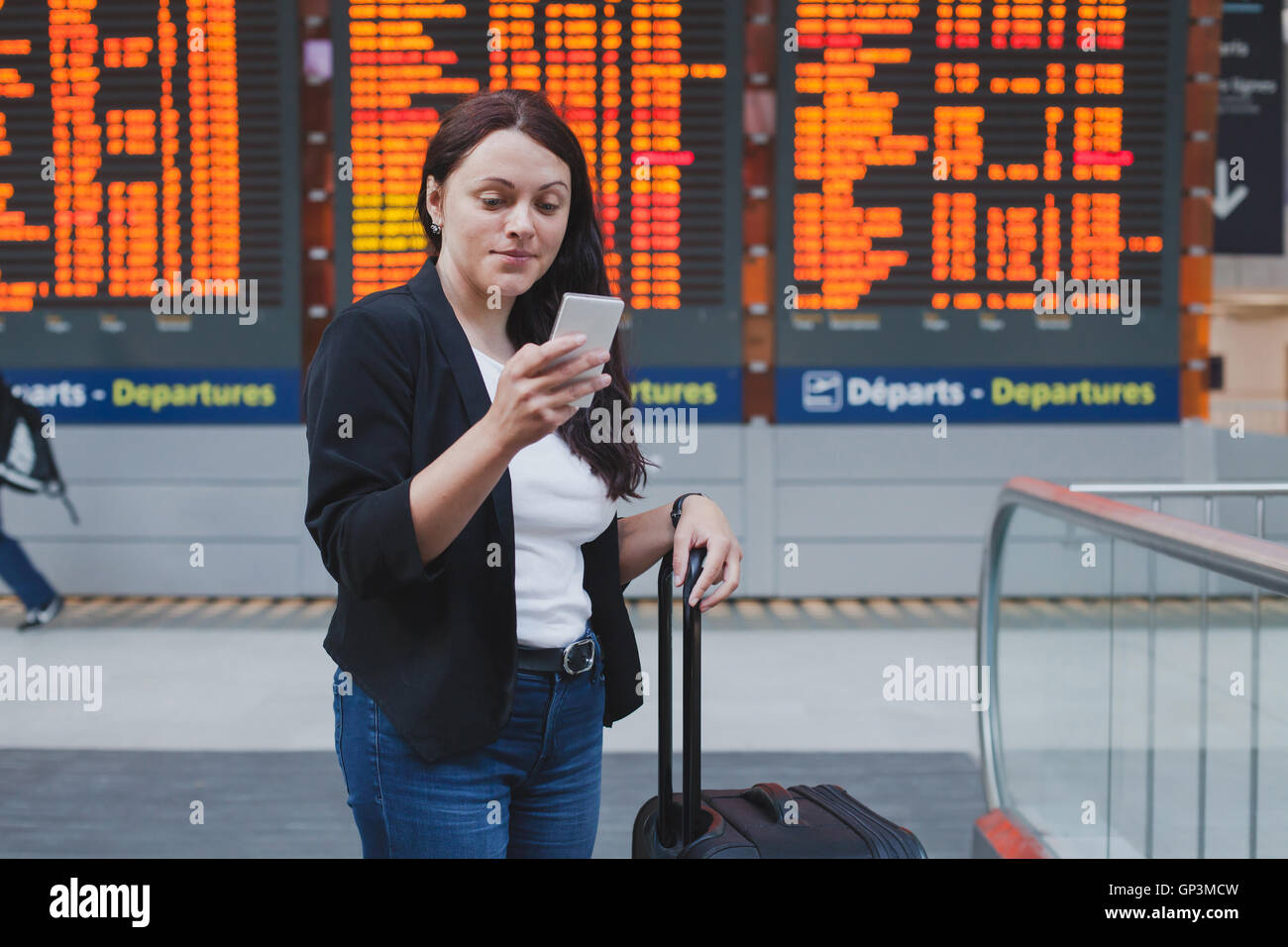 woman with smartphone in international airport checking timetable of the flight - Stock Image