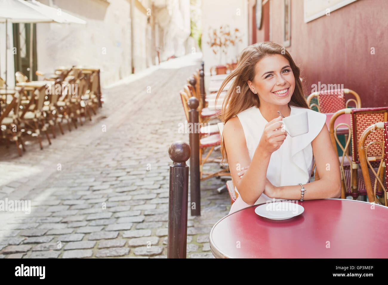 smiling woman drinking coffee in street cafe - Stock Image