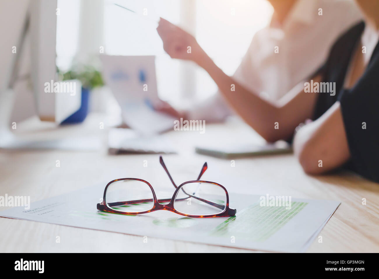 business team discussing project near computer, focus on glasses on foreground - Stock Image