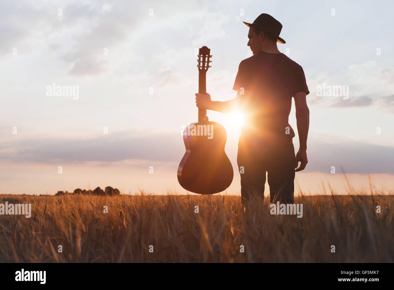 silhouette of musician with guitar at sunset field - Stock Image