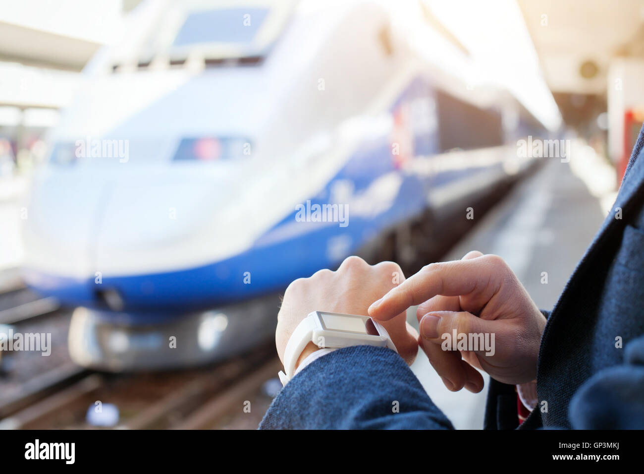 passenger using smart watch at train station - Stock Image