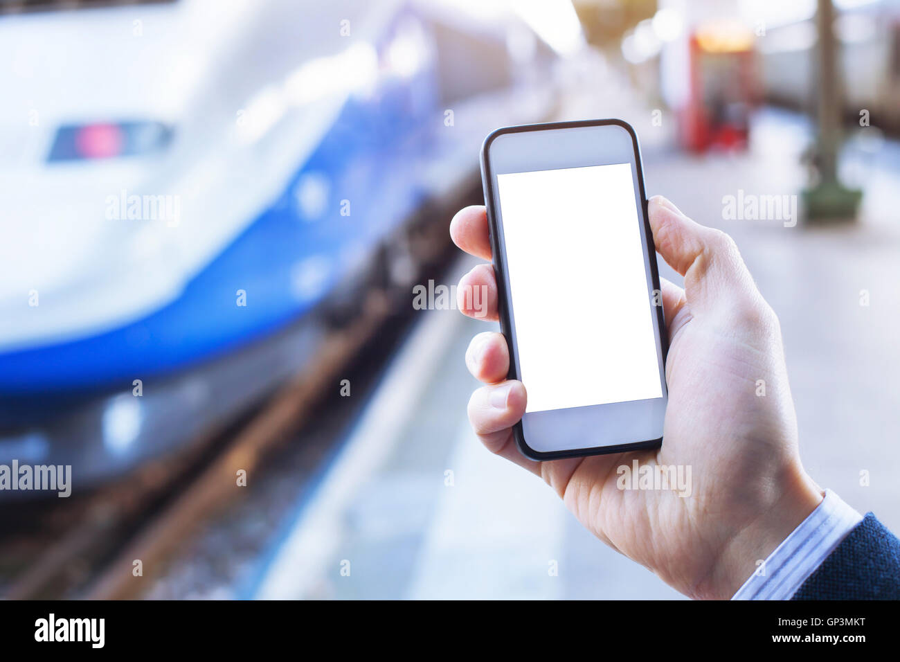 hand holding smartphone with empty blank screen in train station - Stock Image