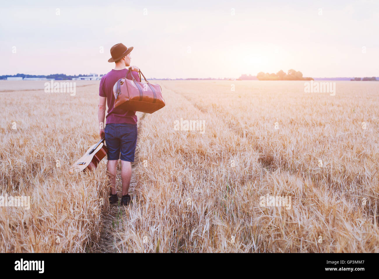 young son leaving home, romantic travel background, man with guitar and road bag walking at sunset field - Stock Image