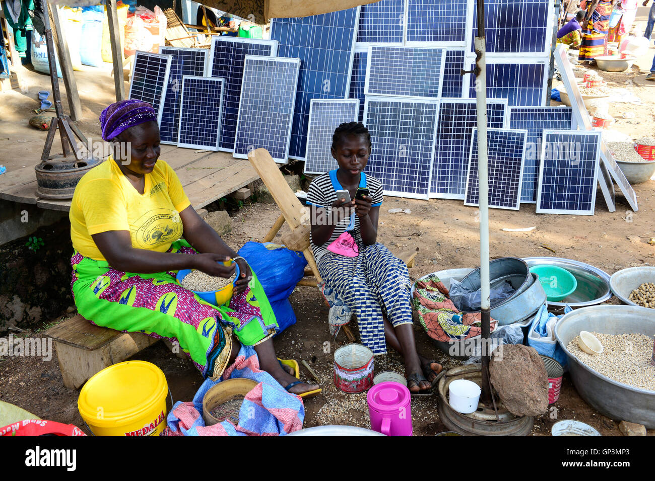 BURKINA FASO, Provinz Poni, Gaoua, weekly market with food crops and solar panels, girl playing with mobile phone Stock Photo