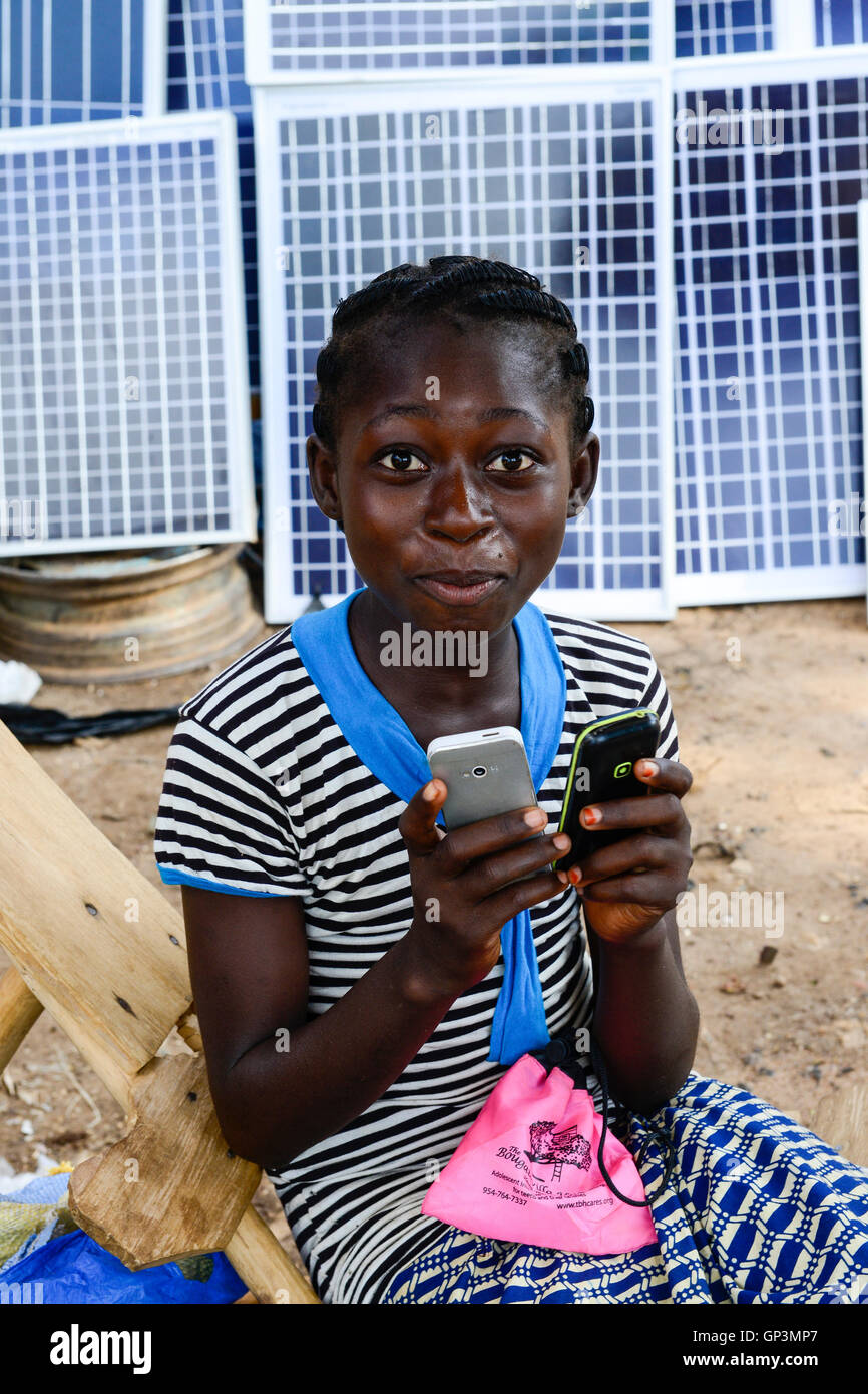 BURKINA FASO, Provinz Poni, Gaoua, weekly market with food crops and solar panels, girl playing with mobile phone - Stock Image