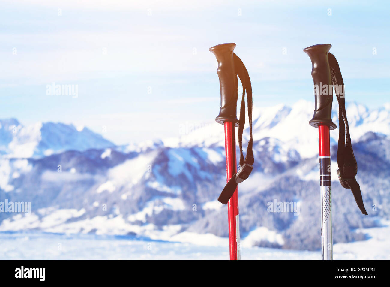 skiing in Alps, close up of two ski poles on mountains background - Stock Image