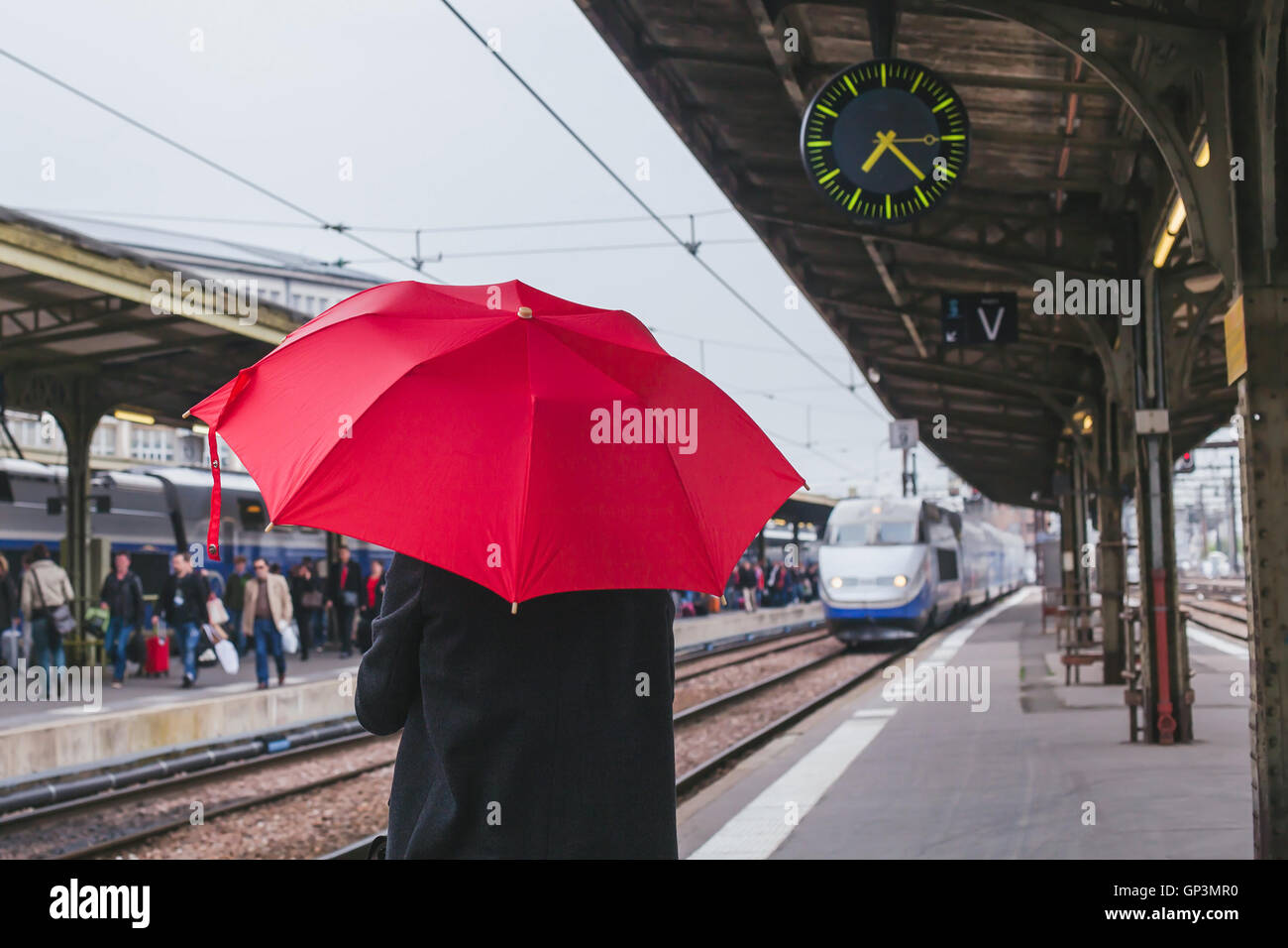 passenger waiting for the train on the platform of railway station - Stock Image