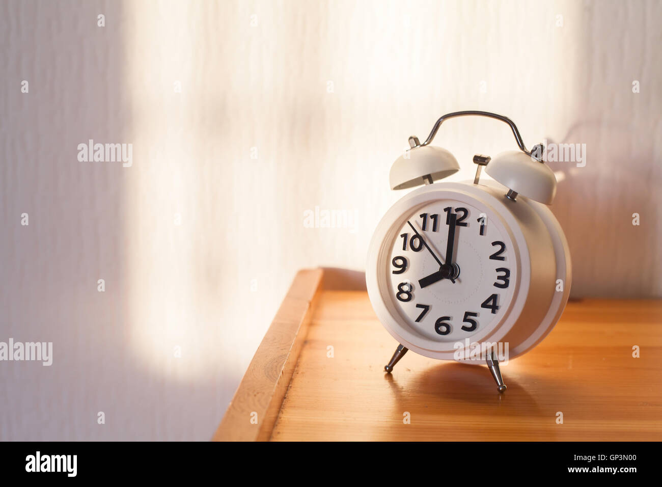 eight o'clock in the morning, alarm clock on bedside table Stock Photo