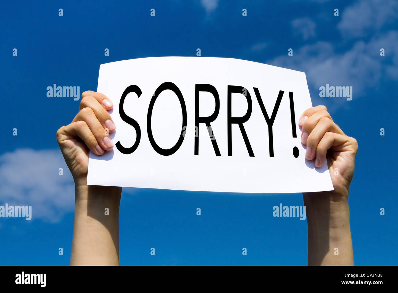 sorry, concept, hands holding sign in blue sky - Stock Image