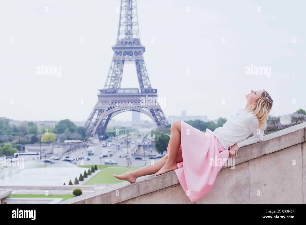 romantic girl in Paris, fashion woman looking up near Eiffel tower - Stock Image
