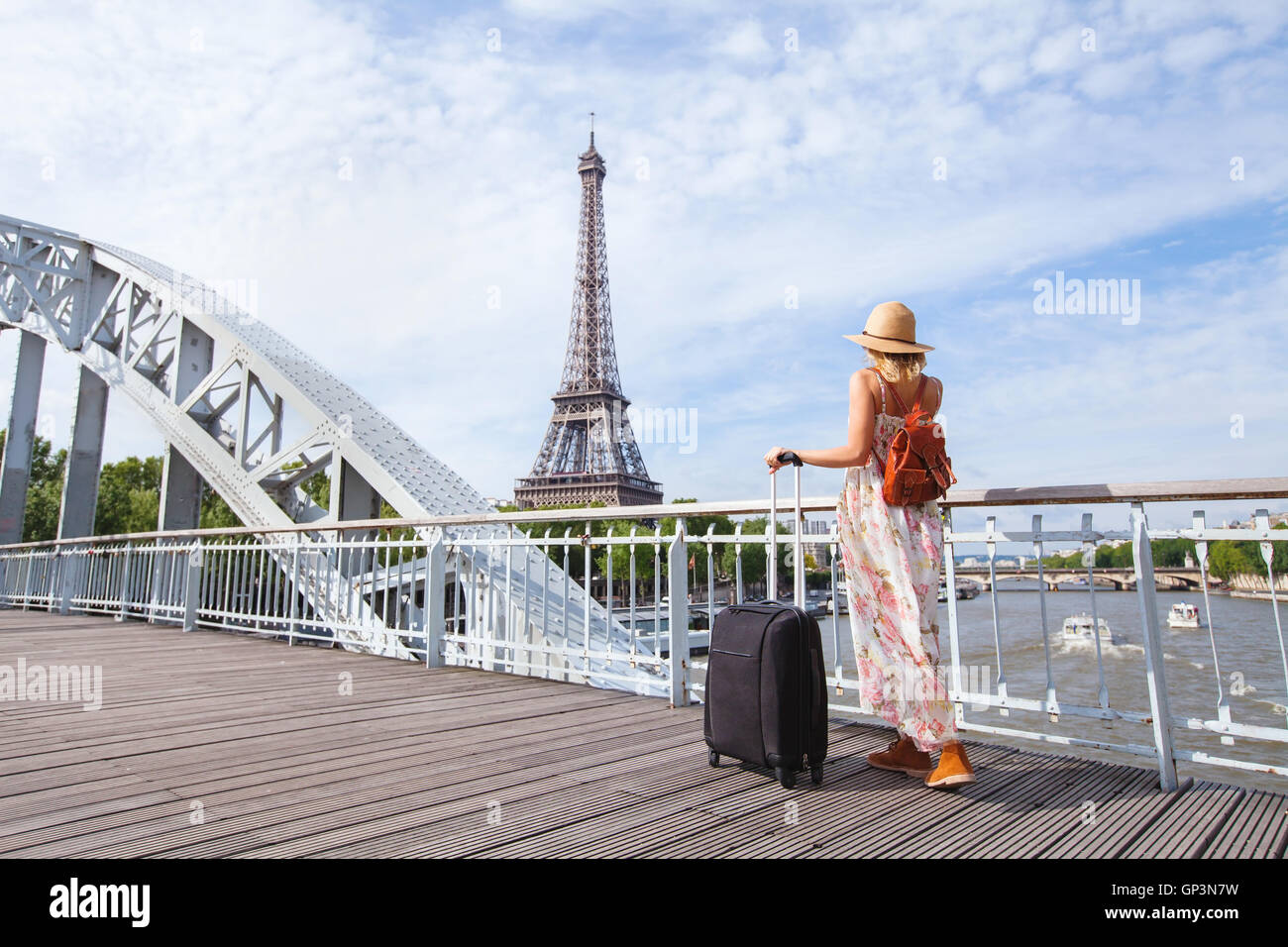 travel to Paris, Europe tour, woman with suitcase near Eiffel Tower, France - Stock Image