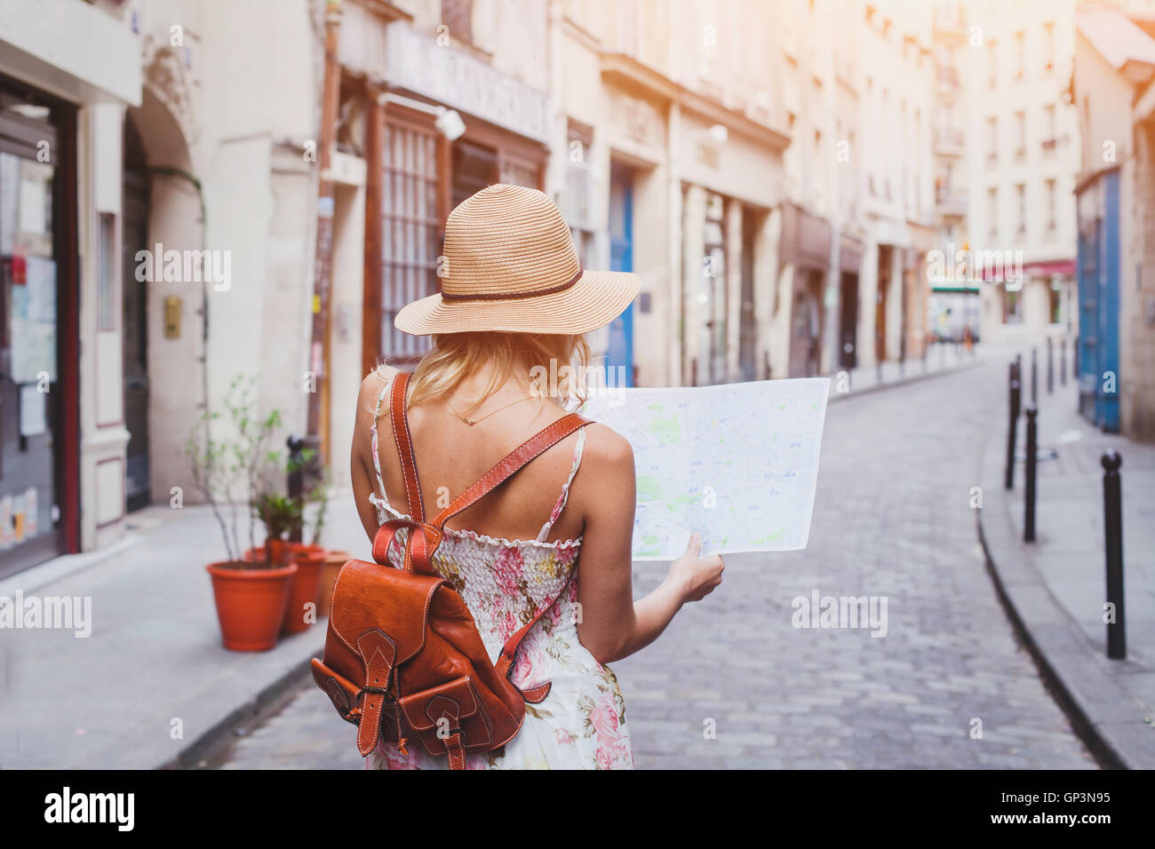 travel guide, tourism in Europe, woman tourist with map on the street - Stock Image