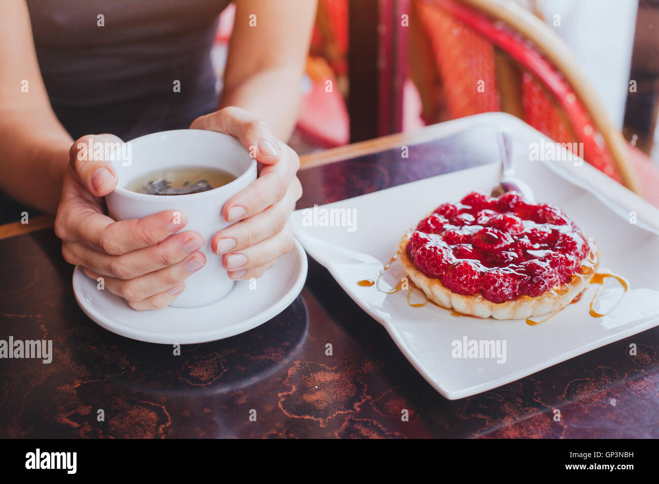 drinking tea with sweet dessert in cafe, close up of hands with cup and fruit cake - Stock Image