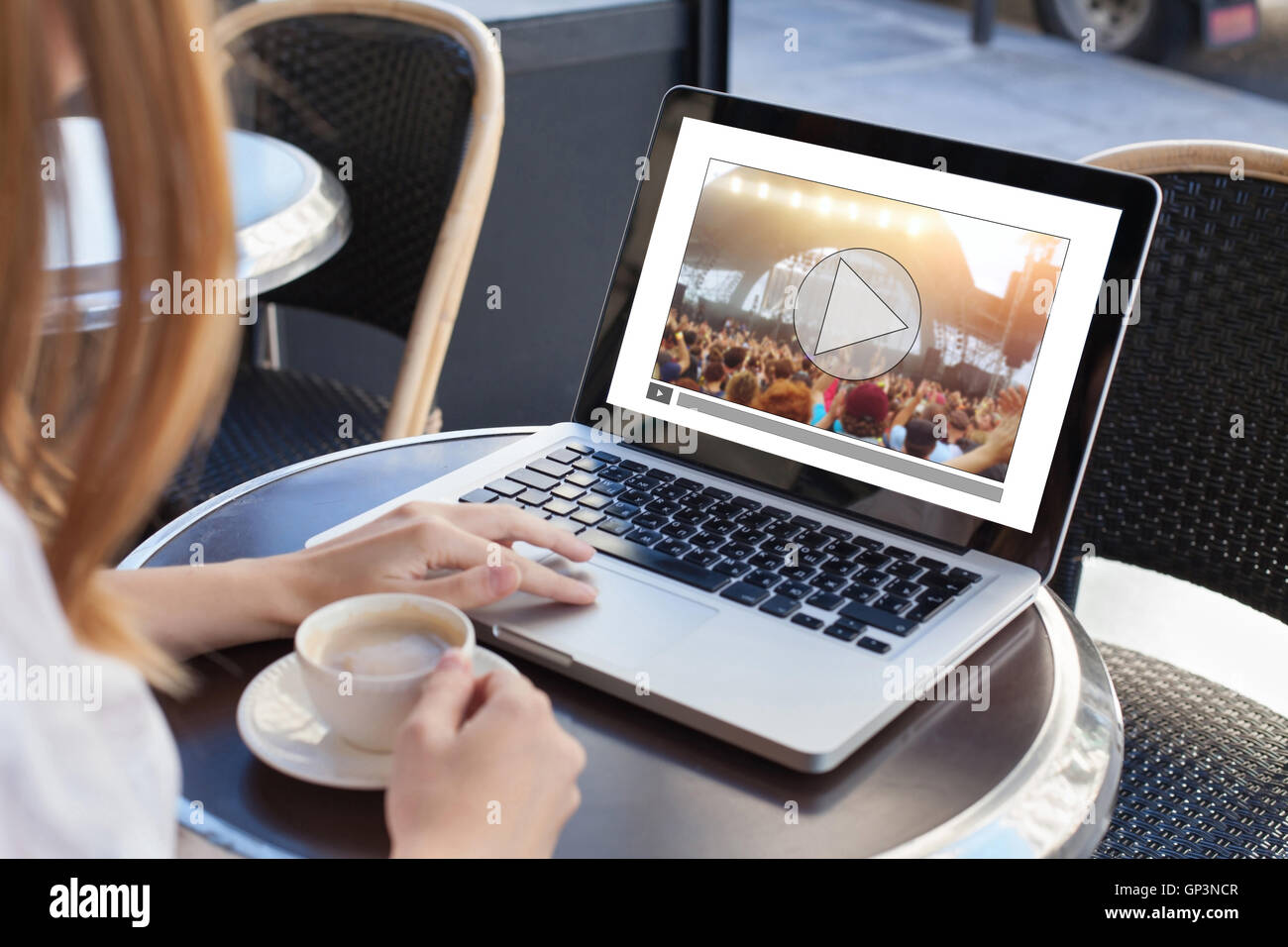 video streaming, online concert, woman watching live music clip on internet on laptop in cafe - Stock Image