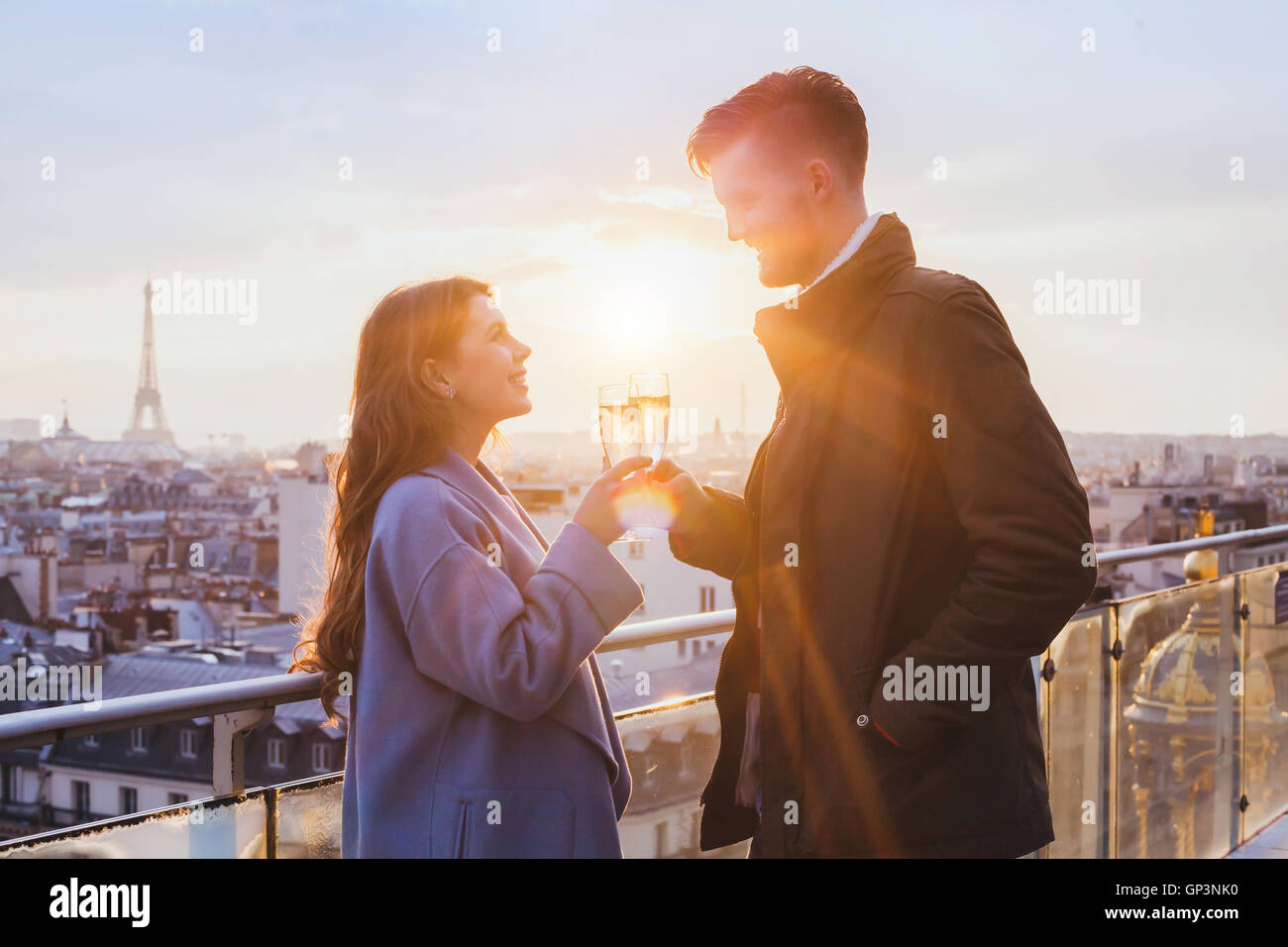 happy couple drinking champagne and smiling at sunset in Paris, celebration - Stock Image