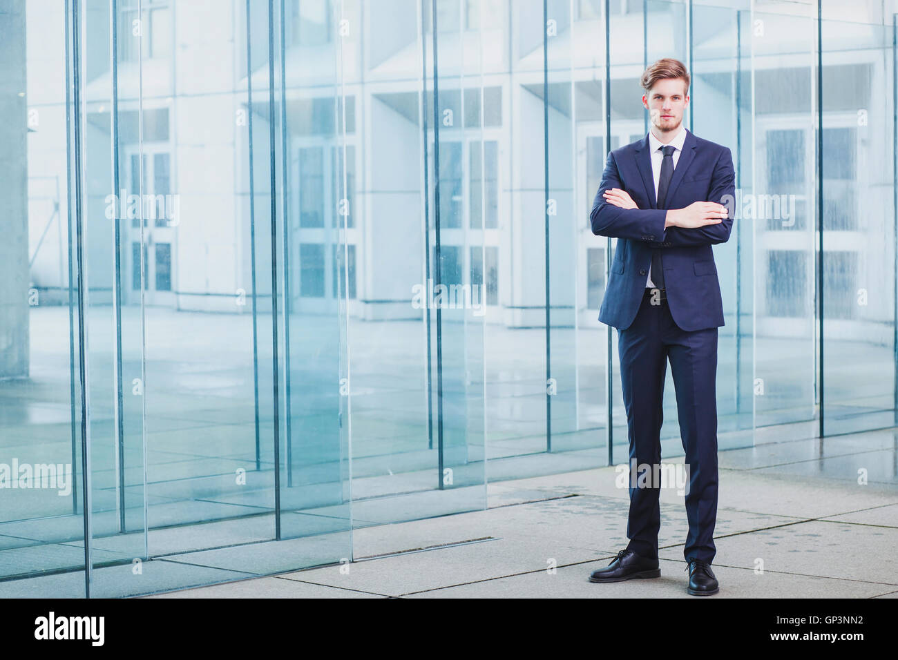 businessman standing on abstract business background, full body portrait - Stock Image