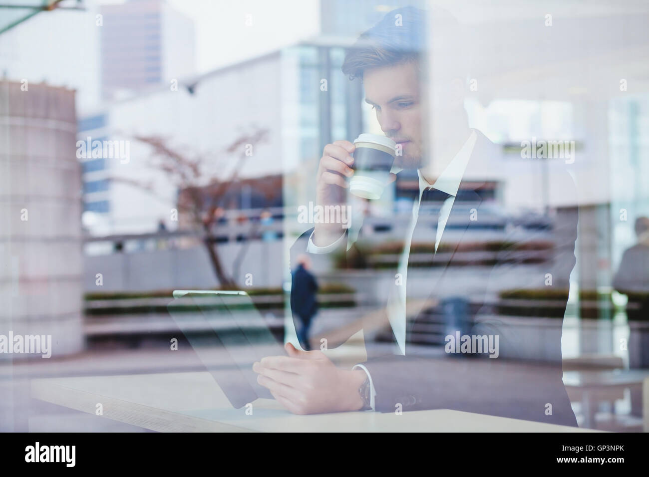 businessman reading news online and drinking coffee in airport cafe - Stock Image