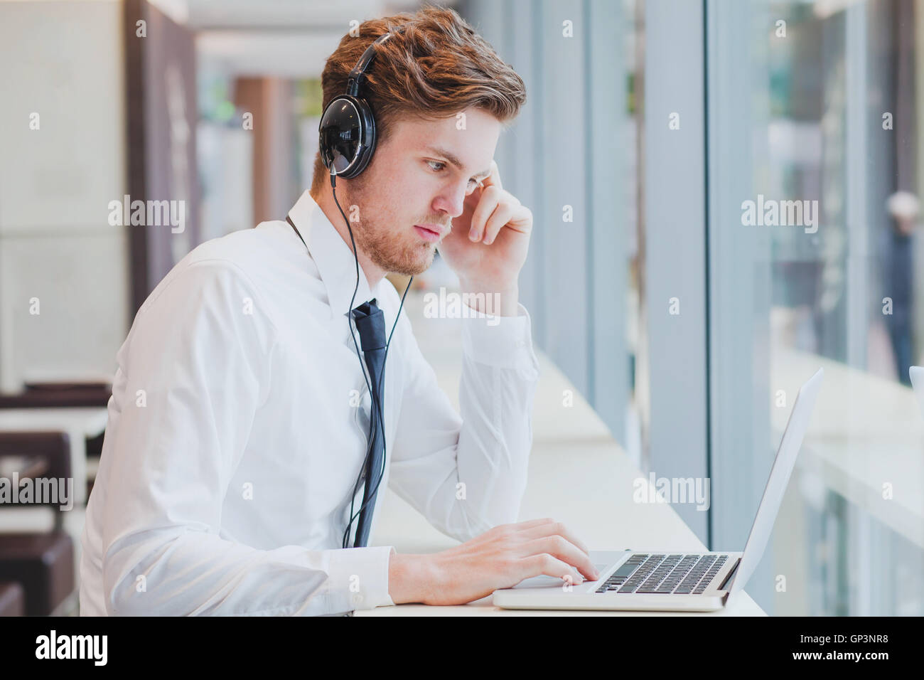 businessman in headphones working with laptop in modern cafe interior - Stock Image