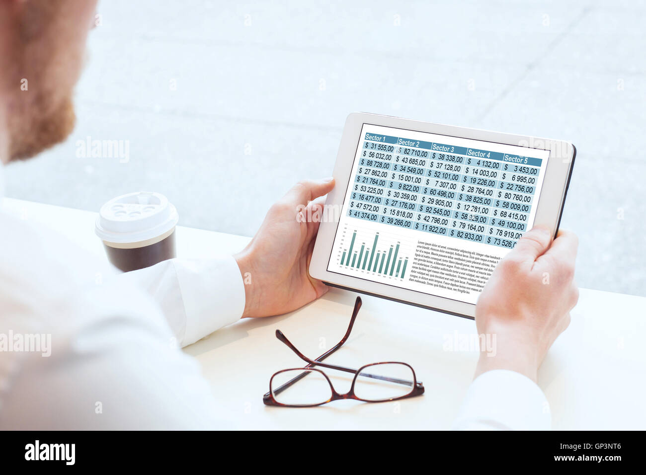 business man reading financial report on tablet - Stock Image