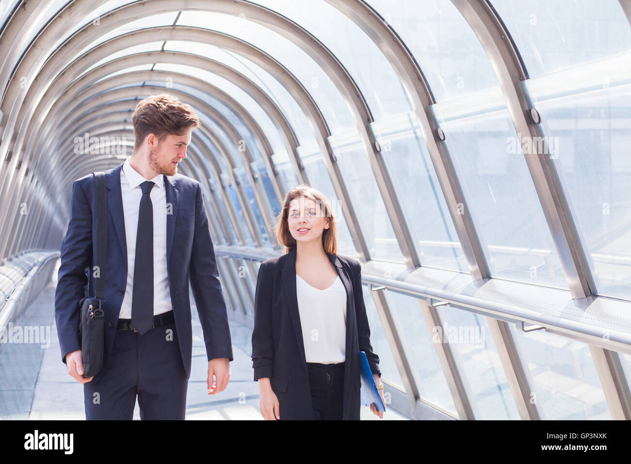 business people walking in office corridor interior - Stock Image