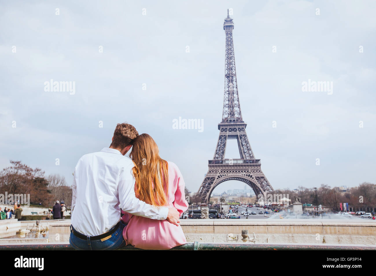 romantic couple looking at Eiffel tower in Paris, honeymoon background - Stock Image