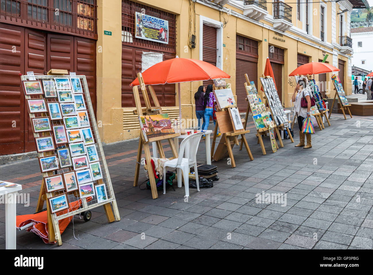 Hand painted art pieces and postcards for sale as souvenirs on the street of historic old city Quito, Ecuador. - Stock Image