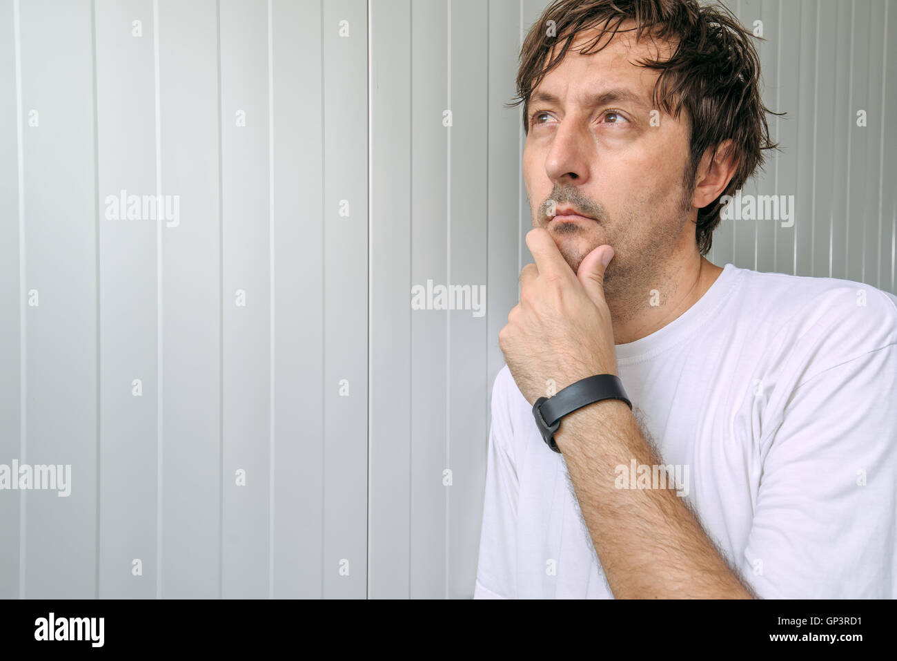 Man with hand on chin thinking deep thoughts and making tough decisions - Stock Image