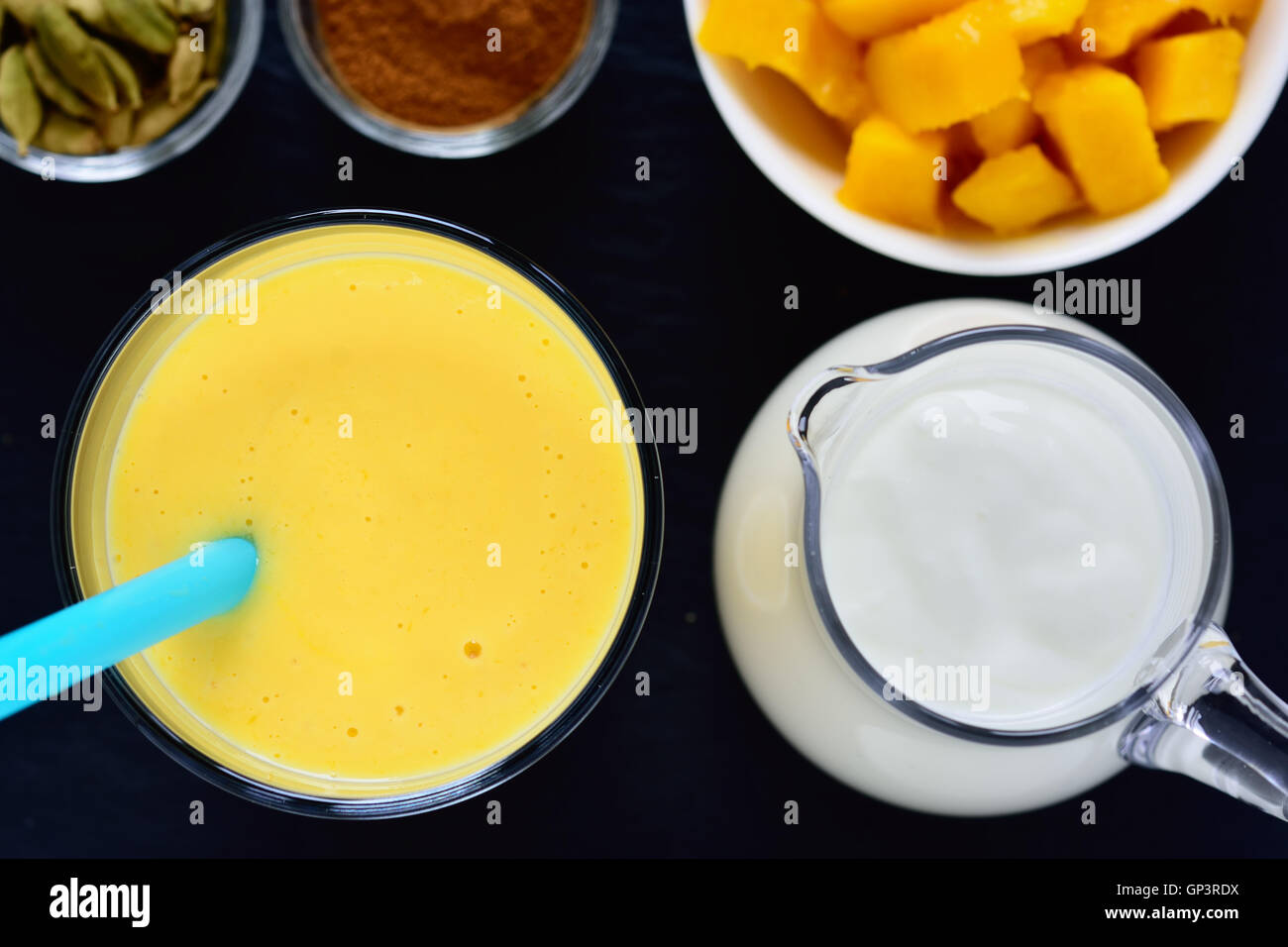 Mango lassi. Mango smoothie made with mango and yogurt, yoghurt. Selective focus. Top view. - Stock Image