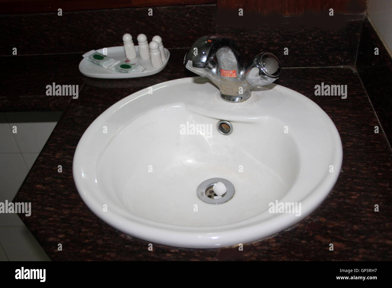 White china clay wash basin with faucet for hot and cold water and other cleaning accessories - Stock Image